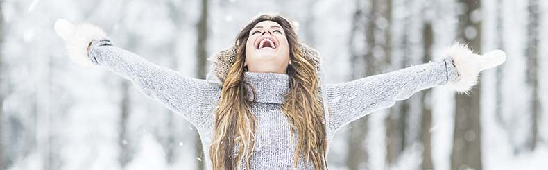 Flicka sträcker ut armar när det snöar